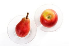 Red pear and red apple in glass bowl. On white background Stock Images