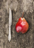 Red pear and vintage knife on old wooden table Royalty Free Stock Photos