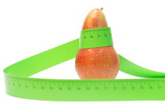 Red pear wrapped in a measuring tape. Close-up of a red pear with a measuring tape around it Stock Photos