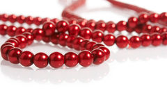 Red pearls on white. Red pearl necklace on white background Royalty Free Stock Image