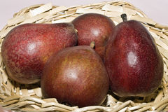 Red pears. A close up of four red pears in a wicker basket Royalty Free Stock Image