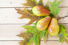 Red pears and autumn yellow maple leaves on a wooden table, close up Stock Photo