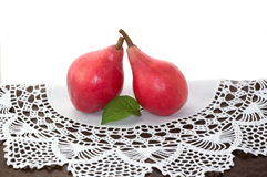 Red pears on old lace doily Royalty Free Stock Image