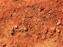 Red pebble on soil background. Red pebble and gravel on red soil Stock Photo