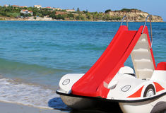 Red pedalo boat with slide on the beach. Photo of red pedalo boat with slide on the beach royalty free stock photography