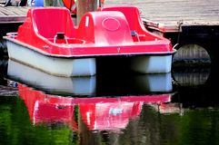 Red pedalo reflecting in water Stock Photos