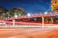 Red pedestrian bridge above the street at night. Red pedestrian bridge above the street. Light trails from the cars passing on the street. Red bridge at night of stock image