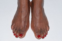 Red pedicure female feet on a white backgrou Royalty Free Stock Photos