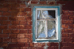 Red peeled off brick wall with window in wooden frame. Red peeled off brick wall with old obsolete window in faded painted wooden frame closed by reflecting Royalty Free Stock Photos