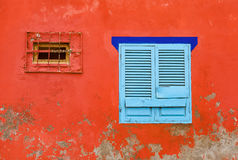 Red, peeling  facade and a blue wooden window. A radiant red, partially peeled off  facade, a large light window with a closed, light blue shutter and a dark Stock Photography