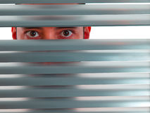 Red peeping Tom. A red man looks to the camera through the blinds Royalty Free Stock Image