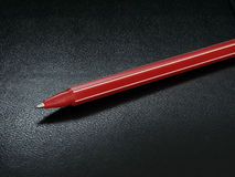 Red pen. Red ballpoint pen at the black leather background Stock Images