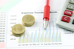 Red Pen,Calculator and money Coins on the Business graph. Royalty Free Stock Images