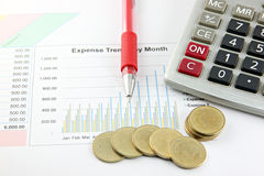 Red Pen,Calculator and money Coins on the Business graph. Stock Photo