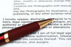 Red Pen and Contract. A pen rests on a release contract with focus on a few lines of legal text Stock Images