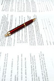 Red Pen and Contracts. A pen rests on a release contract with focus on the center of the middle document Royalty Free Stock Photo
