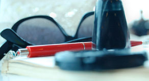 Red pen laying on notebook, sunglasses and other stuff, blurred. Red pen laying on notebook, sunglasses and other stuff Royalty Free Stock Image
