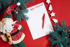 Red pen and notepad on red table decorated with a fir branch. The background for the text. Stock Image