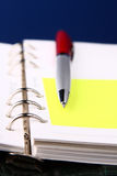 Red pen on an organizer with a selective focus. Red pen and lying on a white open organizer (selective focus Stock Images