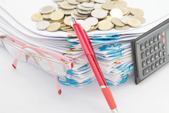 Red pen and pile of paperwork have stack gold coins. Red pen and pile of paperwork with spectacles and calculator have stack of gold coins on a white background Royalty Free Stock Photo