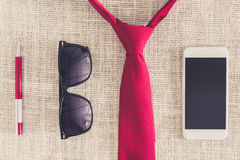 Red pen, smartphone, sunglasses on clean sackcloth with red neck Royalty Free Stock Image