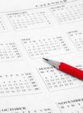 Red pencil. Opened calendar with red pencil on it stock photo