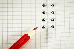 Red pencil on a background of the disclosed notepad. Royalty Free Stock Image