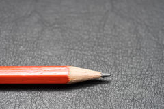 Red Pencil on Black Leather Stock Photo