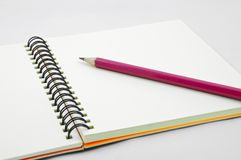 Red pencil on blank page of note book Stock Image