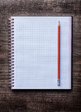 Red pencil and checked notepad on pine wooden Stock Photography
