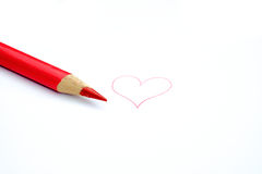 Red pencil crayon and a heart. Red pencil crayon with a hand drawn heart isolated on white background Royalty Free Stock Images