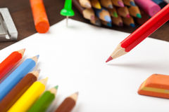 Red pencil draws on white paper sheet Stock Photography