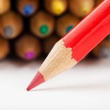 Red pencil draws or writing on paper sheet Royalty Free Stock Photo
