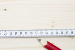 Red pencil and folding ruler lying on wooden board Royalty Free Stock Photo