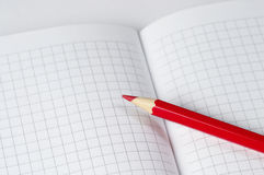 Red pencil. Macro shot over checked paper Stock Image