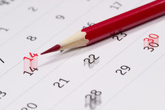Red pencil over calendar. Red pencil over slightly defocused calendar background Stock Photo