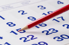 Red pencil over calendar. Red pencil over slightly defocused calendar background Royalty Free Stock Images