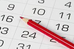 Red pencil over calendar. Red pencil over slightly defocused calendar background Royalty Free Stock Photography