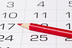 Red pencil over calendar. Red pencil over slightly defocused calendar background Stock Photos
