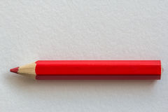 Red pencil on paper. Background Royalty Free Stock Photo
