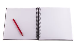 Red pencil placed on notebook. Stock Image