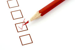 Red pencil and questionnaire on white paper. Royalty Free Stock Image