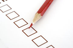 Red pencil and questionnaire on white paper. Stock Photo