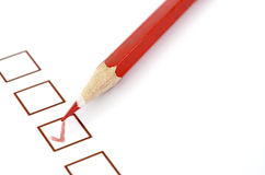 Red pencil and questionnaire on white paper. Royalty Free Stock Photo