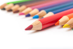 Red pencil in a row of colored pencils close-up Stock Images