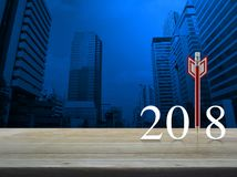 Business strategy happy new year 2018 concept. Red pencil in the shape of a dart with 2018 white text on wooden table over modern office city tower, Business Royalty Free Stock Image
