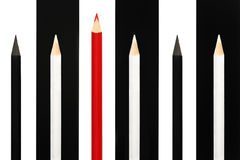 Red pencil standing out from crowd of black and white fellows on bw stripe background. business success concept of leadership uniq Stock Photography