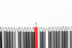 Red pencil standing out from monochrome pencils crowd Stock Photography