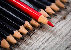 Red pencil stands out from the crowd of black  on a wooden white background. Royalty Free Stock Photos