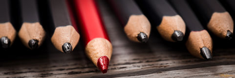 Red pencil stands out from the crowd of black  on a wooden white background. Stock Image